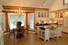 I love this kitchen! The natural wood against the while makes the whole area stand out. Cozy, yet not too rustic. Cabin Style Decorating Ideas - Town & Country Living