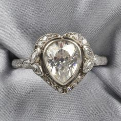 Edwardian Platinum and Diamond Solitaire, bezel-set with a pear-shaped diamond weighing approx. 1.50 cts., further set with marquise- and single-cut diamonds, millegrain and engraved accents