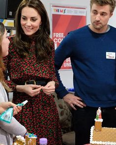 The Duchess chats to volunteers as they get into the Christmas mood by icing gingerbread houses