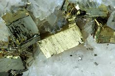Pyrite with Calcite-Dolomite  Aggregate of cubic Pyrite crystals modified by the pyritohedron, some of them unusually elongated. The Pyrite crystals, very bright, are on a matrix with small white Calcite-Dolomite crystals.  Photos by Fabre Minerals