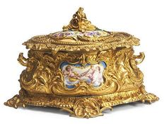 A ORMOLU-MOUNTED SÈVRES STYLE PORCELAIN CASKET WITH HINGED COVER, <br />LATE 19TH/EARLY 20TH CENTURY, <br />the cover and back painted with flowers, the front with putti <br />10in. (25.5cm.) wide, 7 in. high <br />