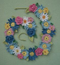 Knot Garden: Flower Garland - combination of 5 different flowers and 2 leaves crocheted  together on a long chain from the back for more stability tack  sides of each flower to the one next  with sewing thread finally  small flowers,  attached on top with French knots.