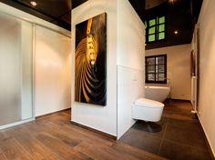 Die spiegelnde Lackspanndecke erzeugt ein spannendes Setting und lässt das Bad zudem noch größer wirken