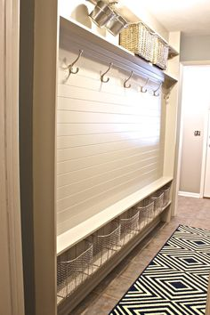 White Wooden Narrow Entryway Bench With Steel Hooks And Rattan Basket Also Steel Racks On Ceramics Flooring