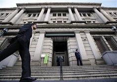 FILE - In this Nov. 19, 2014 file photo, a man walks by the Bank of Japan headquarters in Tokyo. Japan's central bank says sentiment among big manufacturers slipped in the most recent quarter, underlying the shaky footing for the nation's economic growth. The closely watched survey, released Thursday, Oct....