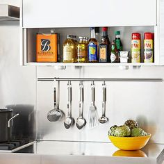 Use a cabinet next to the cooktop to store frequently used cooking spices and oils. Keep counter space free from clutter and hang spoons, spatulas, and strainers on a bar under the cabinet.