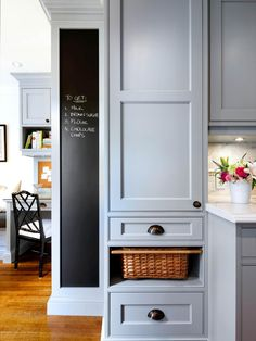 Stunning kitchen features blue cabinets paired with white marble countertops and marble subway tiled backsplash next to built-in pantry cabinets stacked over woven pull-out basket for vegetables situated beside tall kitchen chalkboard. Traditional Furniture, Traditional Kitchen, Solid Wood Countertops, Marble Countertops, Built In Pantry, Kitchen Chalkboard, Kitchen Pictures, Kitchen Ideas, Kitchen Inspiration