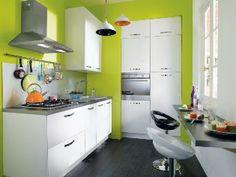 Petite cuisine coloré et lumineuse. Elle est très fonctionnelle grâce aux nombreux placards de rangement. Les placards sont de couleur blanche et totalement contrasté par le vert anis très présent sur les murs de cette cuisine.
