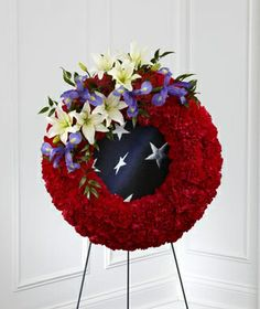 The To Honor One's Country #Wreath is a vibrant patriotic tribute to a fallen soldier. Red carnations form a #gorgeous #wreath, accented with blue iris and white Asiatic lilies, which encircles a blue fabric with white stars on it, in character with the American flag, to create a stunning display for their final farewell service. Displayed on a wire #easel.