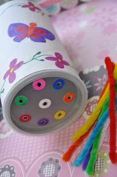 LID HOLE PUNCHED WITH COLORED REINFORCEMENTS AROUD EACH HOLE AND PIPE CLEANERS TO FIT IN THE CORRECT COLOR HOLE
