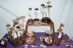 A table full of hand turned bowls and fiber arts tools, including drop spindles, orifice hooks, diz, nostepinne. All handmade by Cynthia D. Haney for Cynthia Wood Spinner