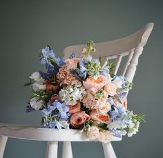 A spring bridal bouquet of Peaches, Coral & Pale Blue created by Eden Blooms Florist for Cain Manor Bride.  Made from Rannunculus, Stocks, Rosemary, Delphinium, Sweet Pea, David Austin 'Juliet' Rose, Muscari & Olive Foliage.  Image by Eden Blooms Florist.