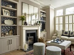 Lily Paulson-Ellis Designs Living Room with antique mirror, joinery with feature back wallpaper and upholstered stools