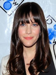Liv Tyler's long hair with curved bangs, rosy cheeks and pinky-coral lipstick   allure.com