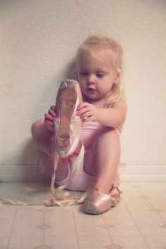 Ohhh! This girl is so cute and  she is looking this pair of pointe shoes as something really interesting.