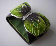... to motyle. Bransoleta wykonana ze srebra 930,  brązowej skóry naturalnej oraz naturalnego 100% jedwabiu w kolorze zielonym. Dwuczęściowa, zapinana z przodu (zapięcie szufladkowe) srebrna forma w kształcie skrzydeł motyla wypełniona ręcznie malowaną skórą o ciekawej fakturze w tonacji brązów, zieleni i seledynu. Całość wykończona brązową skórą a od spodu zielonym jedwabiem. Wymiary motyla łącznie z zapięciem: 11cm ( mierzone z najszerszym miejscu), wysokość ok 2,5 cm (mierzone w ...
