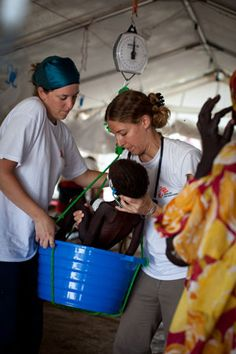 Colleen Laginskie, an MSF nurse [left], and Carolina Nandclares [right], an MSF doctor, weigh Aglash Tadey, 2, in the Intensive Therapeutic Feeding Center at MSF's field hospital in Batil refugee camp. © Nichole Sobecki