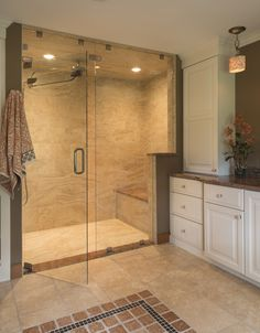 A curbless steam shower with a floor-to-ceiling frameless glass enclosure was installed with a rain-head fixture, built-in shelves, a stone bench and linear drain. | Red House #steamshower #curblessshower