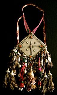 This is a large Turkmen ornament closely related to the gondschuk or breast plate worn by Turkmen women. Both have the same diamond shape, decorated with a cross to symbolize the universe. However, the decoration of this ornament reveals that this particular object was probably not used as personal decoration, but as an amulet for the house or tent.'