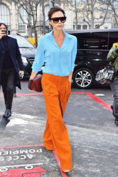 Victoria Beckham wore her namesake brand while out in Paris. She paired a sky blue top with deep orange pants for a contrasted colorful look.