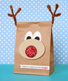 Fun way to package homemade Christmas goodies. Inexpensive paper bag, 3 brown chenille stems as antlers. Use oval cutter on scrapbook paper and add a cute Christmas greeting.