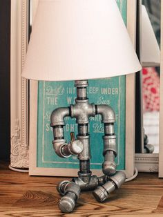 Sitting lady - Table lamp made of galvanized fittings and pipes, utilizing a brass faucet as the switch.
