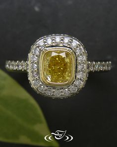Custom halo style ring with bezel set yellow cushion cut diamond and framing round white diamonds - See more at: [http://www.greenlakejewelry.com/gallery/cust_gallery.aspx?ImageID=%2064648#sthash.Xx0HU97v.dpuf]
