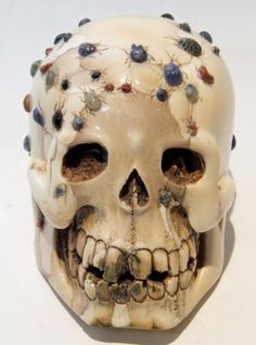 Carved ivory skull with cabochon gemstones polished and decorated to appear as beetles.  The late 20th century or later.  Chinese or Japanese origin.