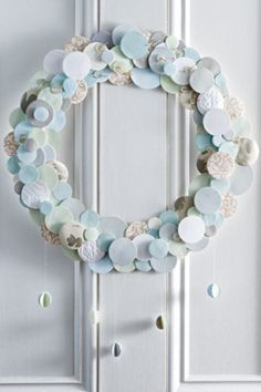 A homemade wreath using paper, wallpaper, button and thread. Why not use off-cuts or recycled Christmas paper?