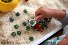Marbles and Rice Sensory play. Practice scooping skills by scooping marbles out of rice.