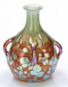 Vase mit vier aus der Masse gezogenen Henkeln - Cytisus (Goldregen) Loetz Wwe., Klostermühle 1902. Mit grün Opal unterfangenes farbloses Glas, umsponnen mit roten Streifen mit fein blauer Äderung. Unregelmäßig über die Fläche verstreute silbrige Flecken. In die Form geblasen. Reduziert und irisiert. Aus dem Körper vier kleine Henkel herausgezogen. Darunter vierfach gedrückt. Ausgeschliffener Abriss. H. 17 cm, D. 11,5 cm. - Lit.: Helmut Ricke (Hrsg). Lötz. Böhmisches Glas 1880-1940. München…