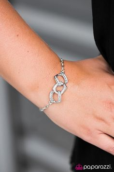 Encrusted in glittery white rhinestones, shimmery silver frames link across the wrist in a refined fashion. Features an adjustable clasp closure.