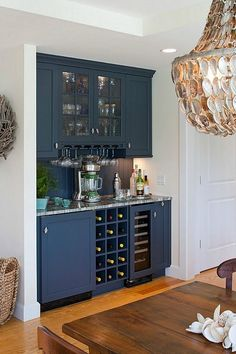 Butler's pantry style home bar built in a Cape Cod kitchen with a blue and white nautical theme to the cabinets and surrounding walls. Lower wine rack, mini refrigerator and locking liquor cabinet with upper storage shelving with both open glass and solid doors. Compare to green malachite design at homebars.barinacr...