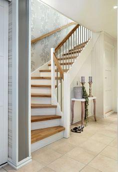 Tapetet Salisbury fra Eijfinger snor seg oppover etasjene, og er kombinert med hvitt panel og gelender og trinn i eik.