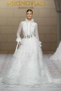 """Brides.com: . Trend: Feathers. """"Carmit"""" two-piece ball gown wedding dress with a sheer long-sleeve top and feather skirt, Pronovias"""