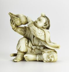 Netsuke of carved ivory, a mountain ascetic (yamabushi) blowing a conch shell, unsigned: Japan