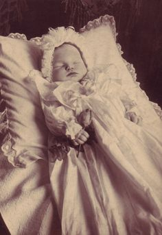 A matt silver print showing a baby dressed in a bonnet and Christening gown, with a rosebud clasped in its right hand.
