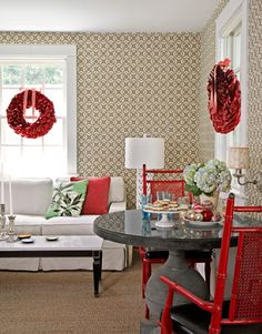 The owner of this Virigina home hung metallic red wreaths over the windows in his living room.   - CountryLiving.com