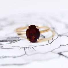 Simple yet stunning, this oval garnet ring was made to turn a head or two. The delicate yellow gold shank brings out the warm red tones of this stone. | Gorgeous Garnet Engagement Rings