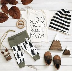 Baby girl tshirt outfit ideas Baby flatlay. All you need is love quote. Baby woodland, tree pattern. Baby boy girl unisex gender neutral baby clothes. Toddler, newborn, kids fashion. Nursery decor mountain theme wood shapes. Grey cream white stripe slouchy beanie. Wooden chew teething toy. Leather baby moccasins. Baby shower gift idea for boy or girl.