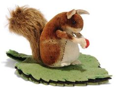 A STEIFF VELVET SQUIRREL PINCUSHION, (3419), brown and white, black bead eyes, felt arms, ears and feet, mohair tail, holding red berry, attached to green and black leaf pin-cushion, circa 1905 --4in. (10.5cm.) long (some small moth nibbles and left flank worn)