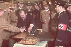The automobile engineer and designer Ferdinand Porsche (in suit) presents Adolf Hitler with a model car during celebrations for Hitler's 50th birthday, Berlin, April 1939.