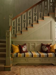 Wood panels glazed in a grayish green hue, a banister sporting a quatrefoil design, and a reclaimed brick floor.
