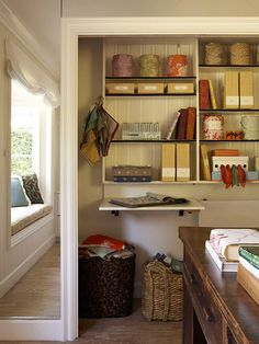Creative Closet  Fashion a creative hub in a wide closet with overhead shelves and a wall-mounted desk. Fabric-covered paint canisters and books are pretty ways to collect project supplies, while swatch baskets below the work surface keep clutter at bay.