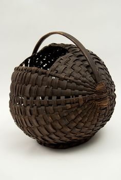 Antique American Pigeon Carrier Basket » Circa 1880-1900: This extremely rare pigeon carrier basket is the most interesting unusual example of early American basketry we have yet to offer to the buying public. With bentwood handle, footed bottom, round construction, and topside opening, this basket was meant to use carry homing pigeons. The construction of this unusual primitve basket is absolutely ingenius.