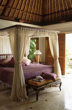 In the image above very decently designed, tropical bedding is shown where a typical organic roof is designed with a canopy bed, comprising of silk curtains. You can sleep with the opened spaces and keep away from flies you can open up the bedding silk curtains. That will let the air move around and you can also sleep peacefully. The room is decorated elegantly with a touch of lilac bed set and mustard small couch.
