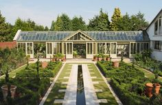 parterre garden with large terracotta pots and a greenhouse