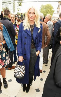 Poppy Delevingne wears a lace top, blue trench coat, skinny pants, fringe boots, and a top-handle Burberry zebra-print bag