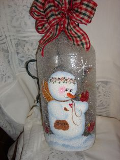 cute snowman holding a red bird lighted wine bottle