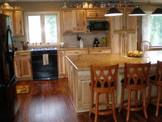 Honey spice hickory cupboards using orange paint color for Acacia wood kitchen cabinets